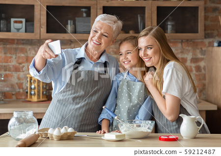 Female family taking selfie on cellphone while cooking together 59212487