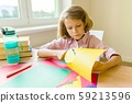 Female child sits at home at the table near the window, scissors colored paper, makes creativity 59213596