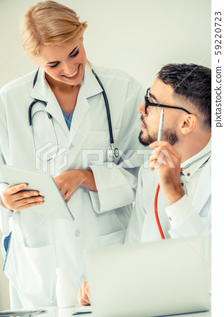 Doctor at hospital works on computer with partner. 59220723