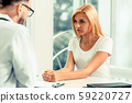 Male Doctor and Female Patient in Hospital Office 59220727