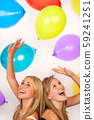 Two beautiful happy teenage girls, female young women, celebrating at a party with colorful balloons 59241251