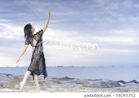 女芭蕾舞演員在日落海岸上跳舞芭蕾舞 59245752