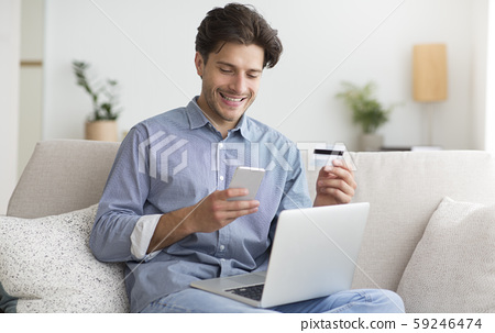 Guy Using Phone, Credit Card And Laptop Providing Payment Indoor 59246474