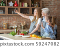 Daughter, mother and grandmother taking selfie while making dinner together 59247082