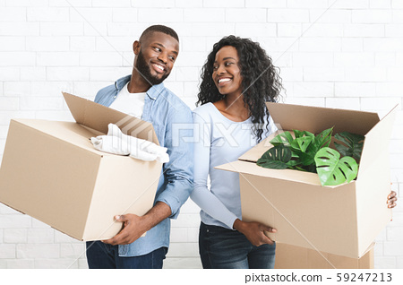 Young couple holding cardboard boxes, smiling to each other 59247213
