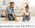 Two adorable girls cleaning carpet at home 59249121