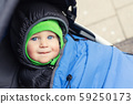 Portrait of cute caucasian toddler boy in black hooded warm insulated dawn overall jacket and blue 59250173