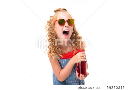 Picture of happy child with fair red curly hair drinks red juice and laugh 59250813