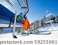 Skier sitting at ski lift. 59255061