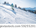 Photo of sports man in helmet with snowboard riding on snowy slope 59255201