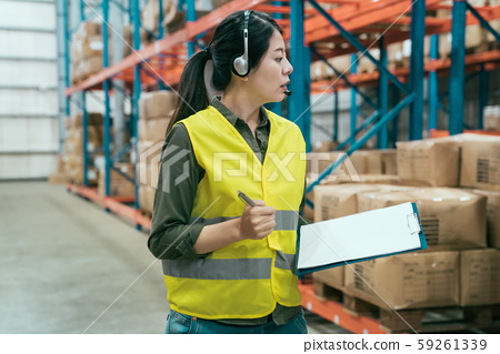 woman talking into headset in large warehouse 59261339