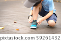 A little healthy asian schoolboy putting on his running shoes by himself in the playground. Life skills, Self-care, Montessori child, Comfortable kids shoes, Sport day, Outdoor fun, Get ready concept. 59261432
