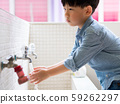 An adorable little asian boy washing his hands before lunch at the wash basin in the kindergarten. Preventing Contagious diseases, Plague. Kids health, Hygiene and hand washing. Saving water. 59262297