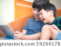 Smart looking asian preteen boy and his adorable little brother laughing together, watch funny cartoon on tablet with joy. Happy Brotherhood Moment, Children with Digital Entertainment, Gamification. 59264178
