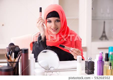 Beautiful woman in hijab applying make-up 59268502
