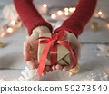Female giving gift box with Christmas decoration and lights 59273540