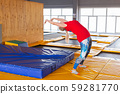 Young woman sportsman on a trampoline in fitness park and doing exercise indoors 59281770