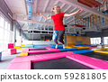 Fitness, fun, leisure and sport activity concept - Young happy woman jumping on a trampoline indoors 59281805