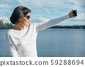 Middle-aged woman blogger takes photos and videos for her blog 59288694