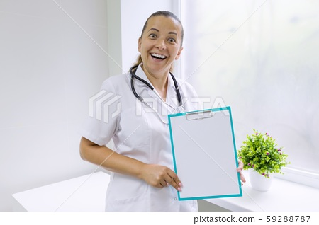 Adult smiling woman doctor with a blank sheet on clipboard for your text, background hospital window 59288787