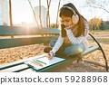 Little beautiful artist drawing with colored pencils, girl sitting on bench in sunny autumn park 59288968