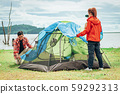 ASian friends setting up the tent outdoor by the 59292313