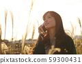 A woman who walks while listening to music in the field of Suki 59300431