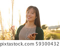 A woman who walks while listening to music in the field of Suki 59300432