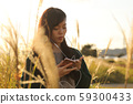 A woman who walks while listening to music in the field of Suki 59300433