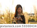 A woman who walks while listening to music in the field of Suki 59300434