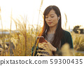 A woman who walks while listening to music in the field of Suki 59300435