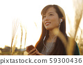 A woman who walks while listening to music in the field of Suki 59300436