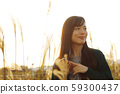 A woman who walks while listening to music in the field of Suki 59300437