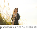 A woman who walks while listening to music in the field of Suki 59300438