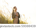 A woman who walks while listening to music in the field of Suki 59300439