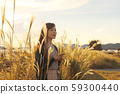 A woman who walks while listening to music in the field of Suki 59300440