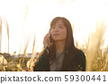A woman who walks while listening to music in the field of Suki 59300441