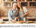 Pretty woman spending time with her old mom at kitchen 59303501