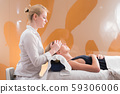 Professional female masseur giving relaxing massage treatment to young female client. Hands of 59306006