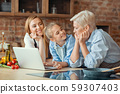 Daughter, mom and granny looking for new culinary ideas online 59307403