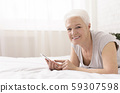 Cheerful senior lady lying on bed and reading text message on cellphone 59307598