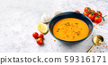 A blue plate with red lentil soup with vegetables 59316171