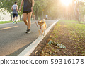 Soft focus with young woman walking with her dog breed Akita inu in the park. 59316178