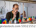 Young worker at the tailor's factory who controls the spools 59321552