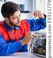 The young repairman fixing and repairing microwave oven 59321779