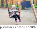 Happy child girl on swing in sunset fall. Little 59322892