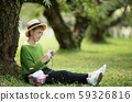 Middle aged Asian woman sitting under the tree and knitting in the park 59326816
