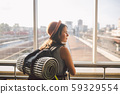 Traveler Rear view woman standing at the window in hall Train Station departure with backpack 59329554