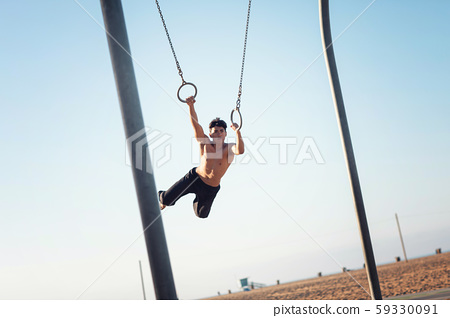 A young man athlete working out on traveling rings 59330091