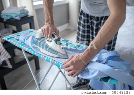 Close up of man using new iron while ironing shirt 59345188